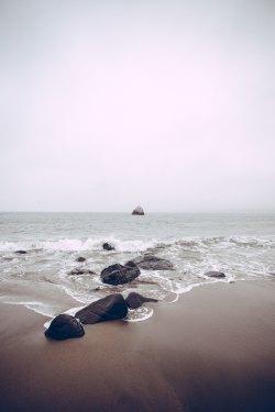 (rocks on sea side at daytime) Photo by Tj Holowaychuk on Unsplash