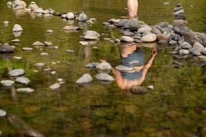 A plus-size white woman wades into the water of a river near some gently rounded river stones sticking out of the water. Her back is toward the camera. She has long brown hair and is wearing a dark blue two-piece bathing suit. Photo from bodyliberationstock.com.